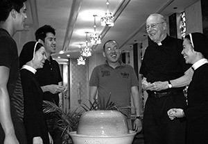 Fr Bill Shea laughing with Divine Word College students in the main chapel