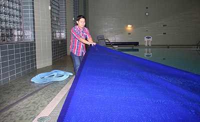 Lifeguard Thinh Nguyen, places the new cover over the DWC pool